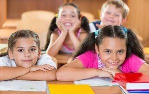 Happy schoolchildren during lesson in classroom