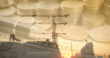 Double exposure gold coins money and construction background. for economy investment finance and banking concept.
